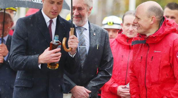 Prince William is presented with a bottle of Bushmills Whiskey