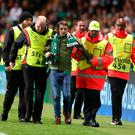 Celtic fan John Hatton is led off the pitch after attempting to kick PSG's Kylian Mbappe