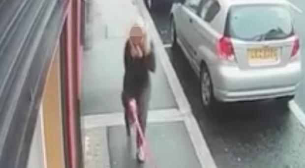 The footage shows a woman kicking the pup as she walks along Union Street in Lurgan