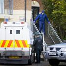 Police forensic experts at the scene yesterday after a woman's body was found at a property in west Belfast