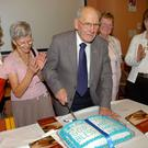 The late Mick Grimes cutting a cake at the launch of his book in Omagh Library