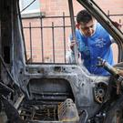 Lacatus Alin examines his burnt-out minibus after three vehicles in the east Belfast area were targeted in hate crimes