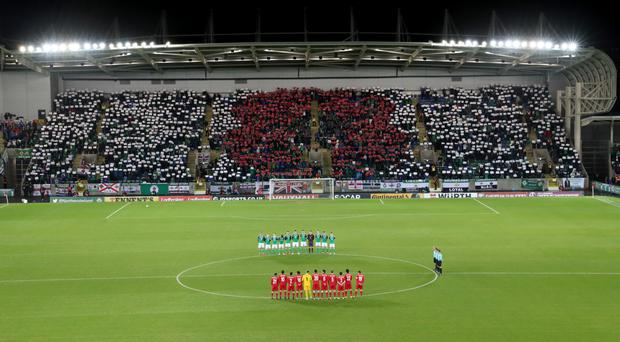 Northern Ireland and Azerbaijan players line up as fans hold up cards to reveal a poppy in 2016.