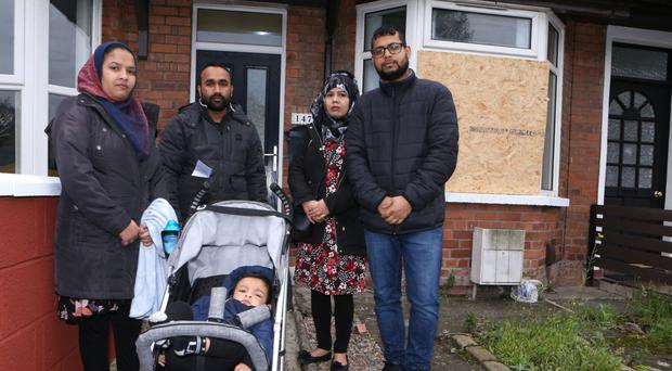 Mr Rahman with his wife and friends outside the home on York Road in north Belfast after it was attacked on Thursday night