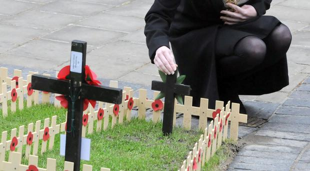 Lord Mayor of Belfast Nuala McAllister places a cross during the official opening of the 2017 Field of Remembrance at Belfast City Hall yesterday