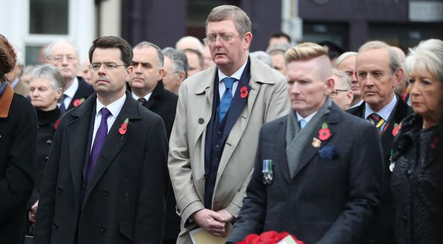 James Brokenshire, left, looks on as Stephen Gault, whose father Samuel was killed in the Enniskillen bombing, lays a wreath
