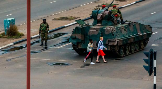 Women walk past Zimbabwean soldiers as they regulate traffic in Harare