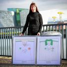 Karen McGarvey outside Belfast Telegraph House with framed Northern Ireland and Republic shirts signed by Paul McGrath and Norman Whiteside