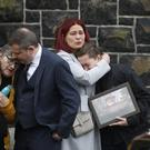 Family and friends comfort each other at the funeral