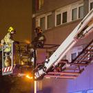 Firefighters tackle the blaze at Coolmoyne House in Dunmurry where residents were evacuated