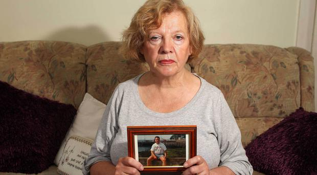 Ann Service holds a picture of her son Brian, who was murdered in 1998