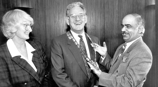 Anna Crane looks on as her husband Bob, former Managing Director of Belfast Telegraph Newspapers, receives his chain of office as incoming president of the Belfast Chamber of Trade in April 1993 from immediate past president, hotelier Diljit Rana