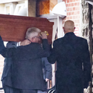 John Dawson's coffin is carried into Roselawn yesterday