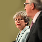 Theresa May listens to European Commission President Jean-Claude Juncker in Brussels yesterday