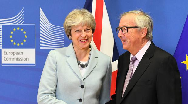 May and Juncker shake hands