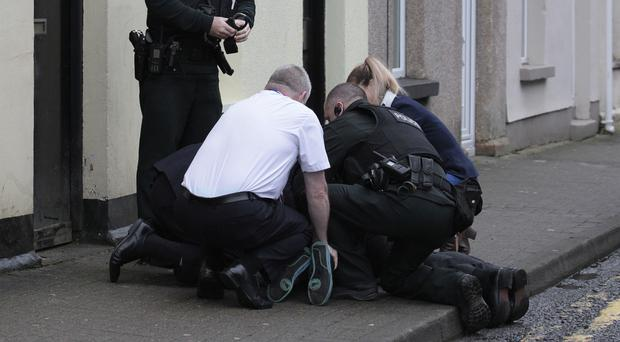 'Police and court security staff pin a man to the ground after the PSNI were called to Ballymena Court yesterday'