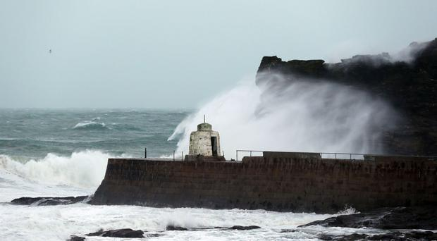 Waves crash against the cliffs in Portreath, Cornwall