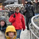 People shelter under umbrellas in pouring rain as they commute to work over Millennium Bridge, Bristol