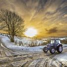 A farmer on his Ford 6810 tractor goes through the snow covered roads of scenic Co Fermanagh