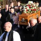 Mourners carry the coffin of Ian Smith to Ardess Parish Hall