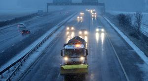 A gritter at work in a snow blizzard (Andrew Milligan/PA)