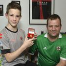 Crusaders fan Mcauley Johnston at home with dad Jonathon and the medal he was given by Stephen Baxter