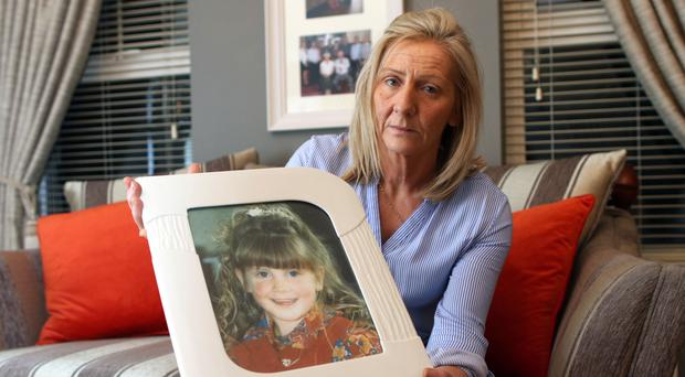Marie Ferguson holds a photo of her daughter Raychel
