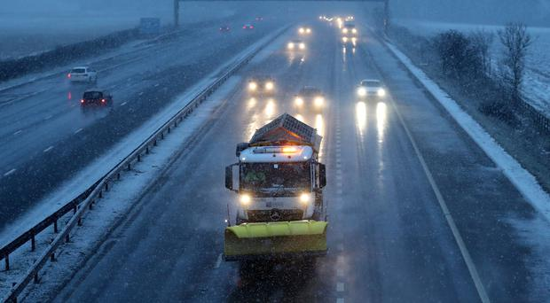 A gritter makes its way along the M9 near Falkirk during a snow blizzard in Central Scotland (Andrew Milligan/PA)