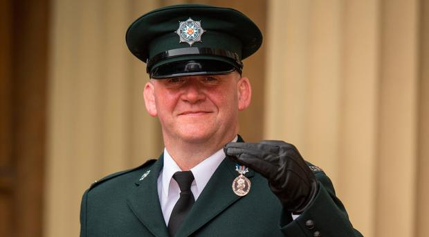 PSNI Sergeant Mark Wright with his Queen's Gallantry Medal, awarded by the Prince of Wales at Buckingham Palace