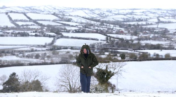 Daniel Murtagh walks up Tullyard Hill outside Crossmaglen, Co Armagh, in the snow (Brian Lawless/PA)