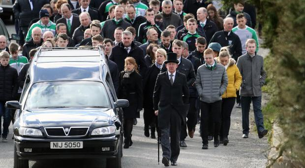 Mourners walk behind the hearse carrying the remains of Niall O'Connor