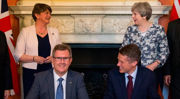 Prime Minister Theresa May stands with DUP leader Arlene Foster (left), as DUP MP Sir Jeffrey Donaldson (second right) and Parliamentary Secretary to the Treasury, and Chief Whip, Gavin Williamson, smile inside 10 Downing Street, London, after the DUP agreed a deal to support the minority Conservative government