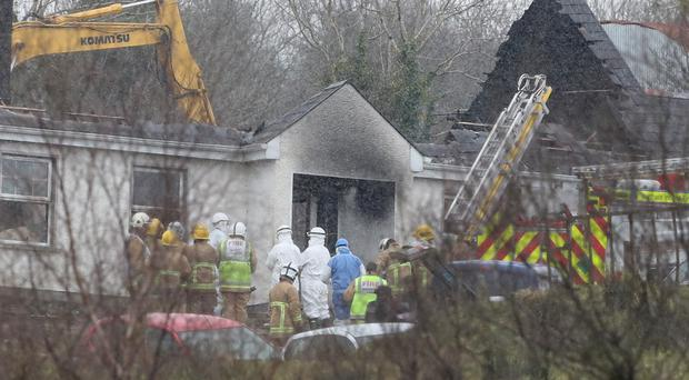 Forensic and fire officers at the house in Derrylin, Fermanagh (Brian Lawless/PA)