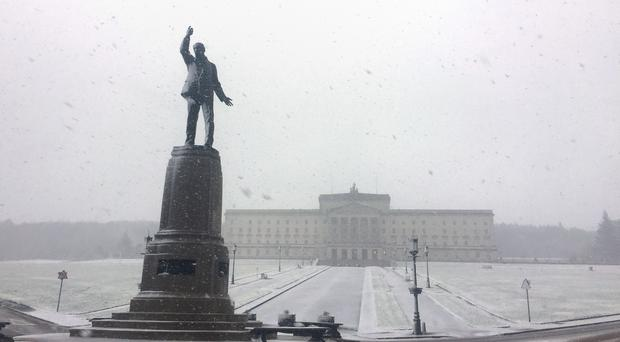 Snow falls on the Carson Statue in front of the Parliament Buildings on the Stormont Estate in Belfast (David Young/PA)