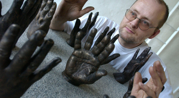 Artist Raymond Watson with his Hands of History artwork