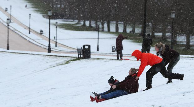 People on sledges on the grounds of Stormont Estate, Belfast (Brian Lawless/PA)