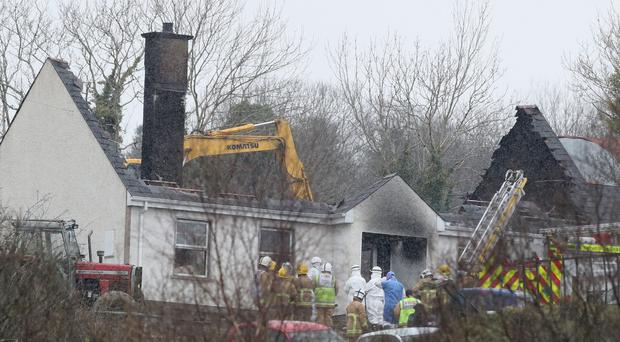 Forensic and fire officers at a house in Derrylin, Fermanagh where four people died in a fire (Brian Lawless/PA)