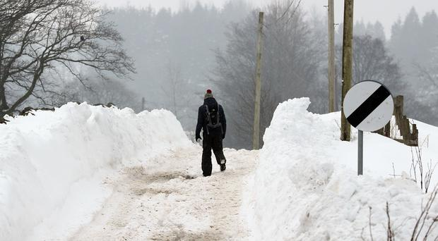 A man walks along the snow covered B818 Denny to Fintry Road