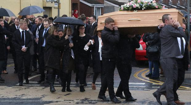 Family and friends carry the coffin of Katie Ballentine from the family home off the Shankill Road