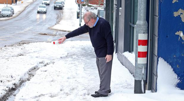A man salts the pavement outside his Banbridge shop during last week's cold snap. As sub-zero temperatures descended schools and businesses were forced to close and there were many problems on Northern Ireland's roads