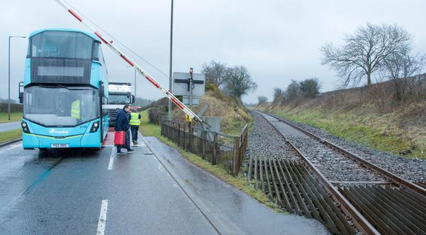 Passengers disembark a Translink Airbus after it got caught beneath a security barrier intended to stop vehicles crossing part of the Templepatrick Road used by trains