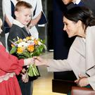 Lleyton Jackson (6) and Rosie Jackson (4) from Ballygowan present Meghan Markle with a bunch of flowers at Titanic Belfast where (below) Prince Harry and his bride-to-be sign the visitors' book