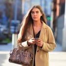 Dara Florence uses her phone on her way to court during the lengthy trial