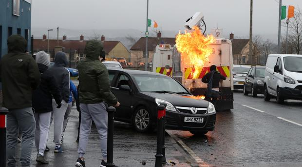 Youths attack police vehicles as they try to prevent Members of Derry 1916 Easter Commemoration committee taking part in an unregistered parade in the Creggan area of Derry (Niall Carson/PA)