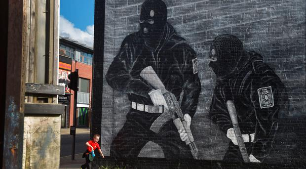 A child runs past a UVF mural
