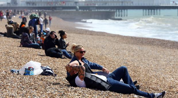 People enjoy the warm weather on the beach in Brighton (Gareth Fuller/PA)