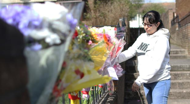 A woman looks at flowers on the Ballysillian road in North Belfast were Lisa Gow was killed