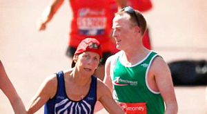 Mark Carey from Belfast helps a woman cross the line in the London Marathon