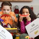 Cole and Sarah showing that £71 of the average monthly family food shop goes on 'treat' foods (Press Eye/Darren Kidd/PA)