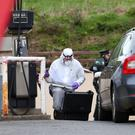 A forensics officer examines the scene following the theft of the ATM